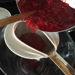Pouring mashed berries into strainer